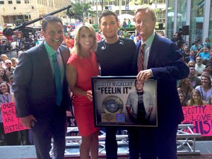 "Scotty McCreery received a Gold Record for his single ""Feelin' It"" after his ""FOX & Friends"" All-American Summer Concert Series performance on July 31. Pictured (left to right): ""FOX & Friends"" hosts Brian Kilmeade and Elisabeth Hasselbeck, McCreery, and ""FOX & Friends"" host Steve Doocy. Credit: Scott Stem"